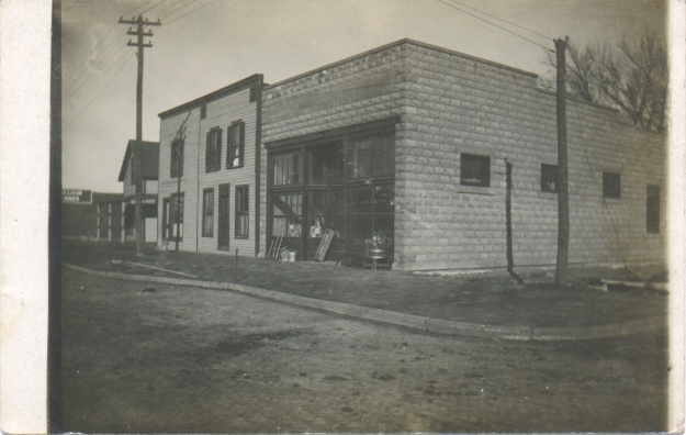 A postcard featuring a building at the corner of 1st and Main in Ottawa, Kansas.