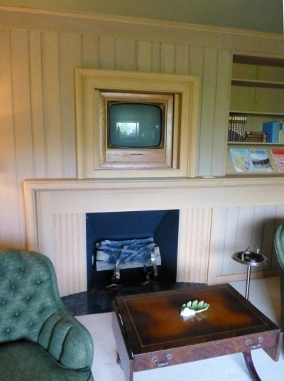 The living room of the future: a television is hidden by a painting that will slide away with the touch of a button. Who needs a real fireplace when you can have an electric one?