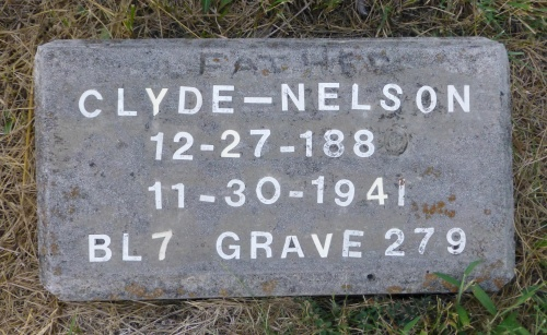 The grave of Clyde Nelson, a father, is one of only two stones bearing a name instead of a number.