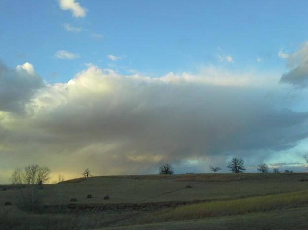 February 20: Large rain clouds drift over the snow-free hills along I-70 near Topeka.